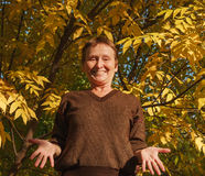 Elder woman shrug shoulder on the background of colorful leaf. Photo took in Moscow, Russian Stock Image