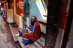 A elder in Varanasi, India. A elder woman sits on the steps in Varanasi, India stock photography