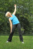 Elder woman stretching before being active Stock Image