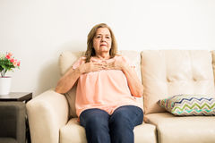 Elder woman suffering heartache. Good looking senior adult lady with her hands on her breast while having a heart disease on the sofa at home Stock Photography