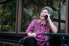 Elder woman talk on mobile phone on terrace. elderly female spea Stock Image