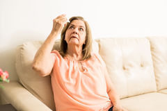 Elder woman using some eye drops. Beautiful aged lady taking care of her eyes with some eye drops while sitting in the living room Royalty Free Stock Photography