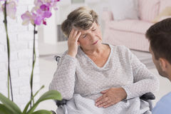 Elder woman on a wheelchair with headache Royalty Free Stock Photo