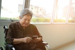 elder woman in wheelchair holding mobile phone. elderly senior using smartphone royalty free stock images