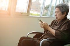 elder woman in wheelchair holding mobile phone. elderly senior using smartphone royalty free stock photos
