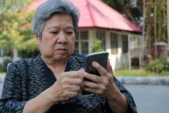 Elder woman in wheelchair holding mobile phone. elderly senior using smartphone stock photo