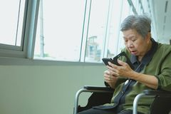 elder woman in wheelchair holding mobile phone surprised shocked stock photos