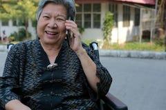 Elder woman in wheelchair talk on mobile phone. elderly senior speaking on smartphone stock photo