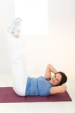 Elder woman working out on mat Stock Photo