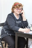 Elder woman at workplace with phone in office Stock Photo