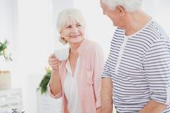 Elder woman is drinking tea. Elder women is drinking tea in kitchen during conversation with husband in striped shirt Stock Image