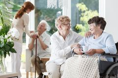 Woman visiting her friend. Elder women in glasses visiting her disabled friend at the senior`s house Stock Photos