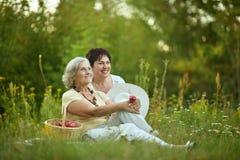 Elder women resting on grass Royalty Free Stock Image