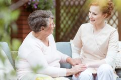 Elder woman sitting in garden. Elder women sitting on garden couch while talking with red haired nurse in garden Royalty Free Stock Image