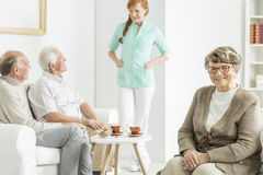 Elder woman smiles. Elder women smiles and sitting on chair while nurse visits retirement home Stock Photo