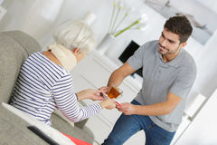 Elder woman taken care by young man Royalty Free Stock Images