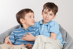 Elder and younger brother sitting on pufe Stock Photos