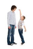 Elder and younger brothers. Younger brother of measuring the growth of an older brother royalty free stock photos