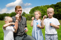 Elder and younger brothers blowing soap bubbles. Elder brother teaches the younger brothers and sister blowing bubbles Stock Images