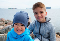 Elder and younger brothers. On the shore of the sea in autumn Stock Photography