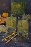 Elderberry flowers and lemon drink. Refreshment healthy elder juice. Glass of elderflower lemonade on wooden rustic board. Alterna. Tive medicine and therapy Stock Images