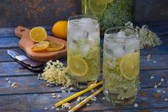 Elderberry flowers and lemon drink. Refreshment healthy elder juice. Glass of elderflower lemonade on wooden rustic board. Alterna. Tive medicine and therapy Stock Image