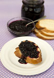 Elderberry jam. On bread and in a small glass bowl Royalty Free Stock Photos