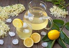 Elderberry juice. Healthy elder flower juice with lemon on wooden background Royalty Free Stock Photography