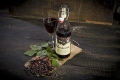 Elderberry wine and elderberries on wooden table Stock Images