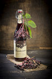 Elderberry wine and elderberries on wooden table Stock Photos