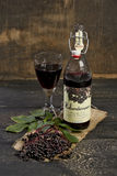 Elderberry wine and elderberries on wooden table Royalty Free Stock Photography
