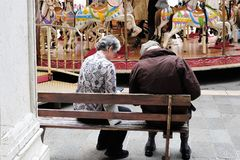 Elderely couple resting on bench in front of merry go round in Treviso, Italy royalty free stock photos