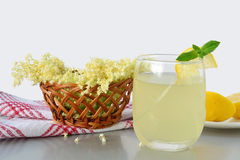 Elderflower flavored summer refreshment. Glass of elderflower refreshing drink and elder-flowers in a basket royalty free stock images