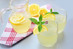 Elderflower juice with lemon. Pitcher and glasses of refreshing elderflower drink with lemon and mint royalty free stock photography