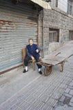 Elderley femelle dehors sur une chaise, Qingdao, Chine Photographie stock libre de droits