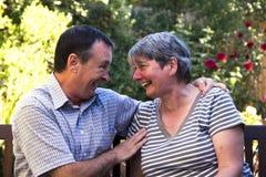 Elderley Paare, die auf einem Banklachen sitzen Stockbilder
