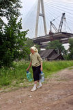 Elderling, der im Haus unter Brücke lebt, geht für Wasser Lizenzfreie Stockfotografie