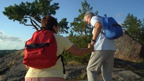 Elderly active couple climbing on the rock and admiring the sunrise, the sunset. Scandinavian landscape with sea and pine trees stock video