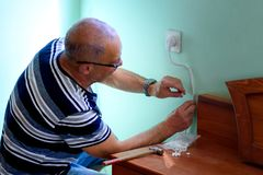 Senior man repairing in the room. royalty free stock photography