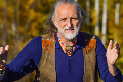 Elderly active man. Elderly, vital, active man dressed in hippie style, showing the length of something in communication; outdoor shoot, autumn sunny day stock photos