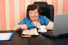 Elderly adult woman reading news Stock Image