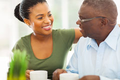 Elderly african man granddaughter. Smiling elderly african american men enjoying coffee with his granddaughter at home Royalty Free Stock Photos