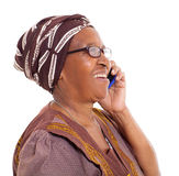 Elderly african woman phone. Happy elderly african woman talking on smart phone on white background Royalty Free Stock Images
