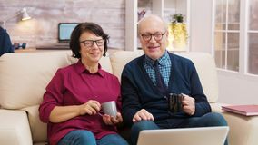 Elderly age couple wave at laptop during a video call