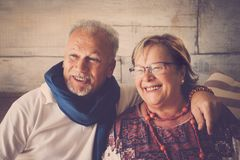 Couple of senior at home smiling. Elderly aged lady and gentleman sit down at home smiling with happiness. love forever together royalty free stock image