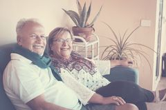 Couple of senior at home smiling. Elderly aged lady and gentleman sit down at home smiling with happiness. love forever together stock image