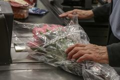 Elderly aged man buying boquet of pink roses at the store - cropped and selective focus.  royalty free stock photography
