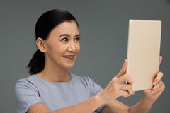 Elderly Aging Society 60s years old using touch. Screen on computer tablet to check website, chat communication with friends and selfie self portrait herself royalty free stock image