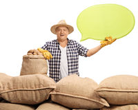Elderly agricultural worker with burlap sacks holding speech bub stock images