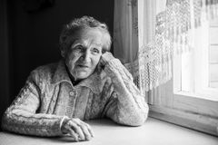 Elderly alone woman portrait contrast of black and white. Elderly woman portrait contrast of black and white stock photography